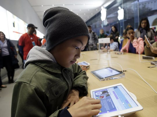Tyson Navarro, 10, of Fremont, Calif., learns to build code using an iPad at a youth workshop at the Apple store in 2013.  Apple says all of its iPads, iPhones and Macs were affected by the chip design flaw revealed last week.
