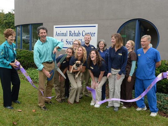 Mark Ledyard, owner of Charlotte Street Animal Hospital, uses giant scissors to cut a ribbon during the grand opening of the Animal Rehab Center and Social Club, an expansion of the hospital, on Thursday, Oct. 1, 2015. The center will provide a safe and engaging place for dogs during the day as well as canine rehabilitation services.