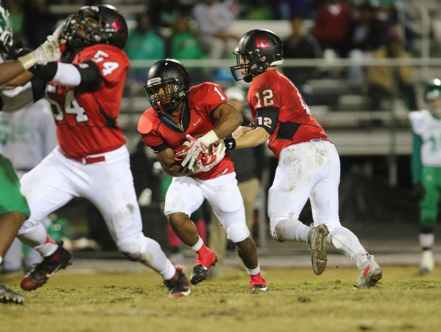 Hillcrest's Collin Sneed(12) hands the ball off to Quintavis Ballenger(1) Friday against Easley.