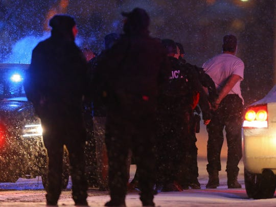 Robert Lewis Dear, far right, shown shortly after surrendering to Colorado Springs police after a long shooting rampage that left three dead.