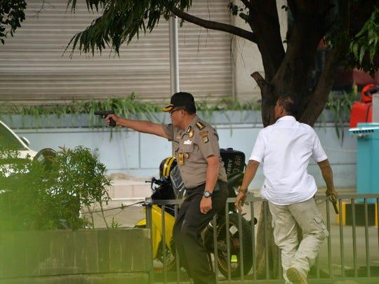 An Indonesian policeman fires his handgun towards suspects