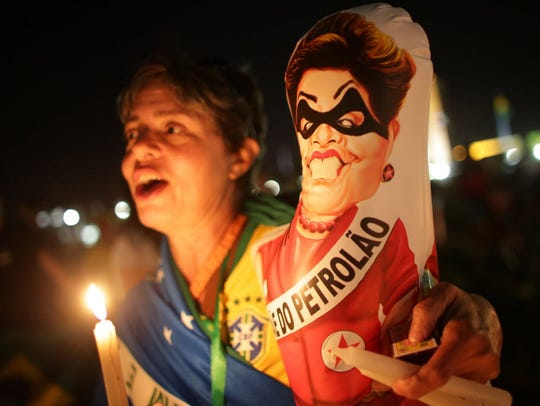 A protester in Brasilia holds a caricature of Brazil's