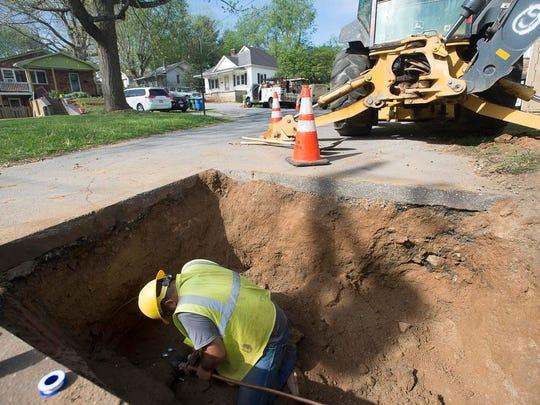 Water maintenance worker, Coltron Gonzalez, works on a new water tap on Thursday on Nebraska Street in West Asheville.