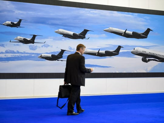 A visitor walks past the stand of Brazilian plane maker