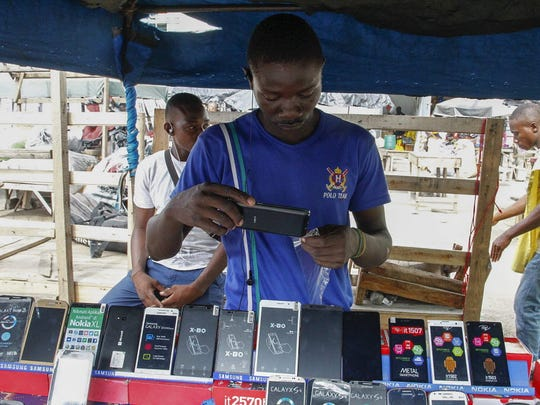 A cellphone vendor on a street side in Abidjan, Ivory Coast. The mobile industry in West Africa has grown from a state controlled space to becoming a massive market fueling economic growth and technological innovation.