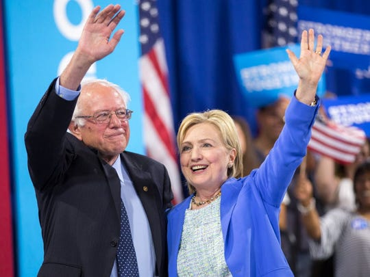 Presumptive Democratic presidential candidate Hillary Clinton and Sen. Bernie Sanders wave after speaking at a rally in Portsmouth, N.H., where Sanders endorsed Clinton on July 12, 2016