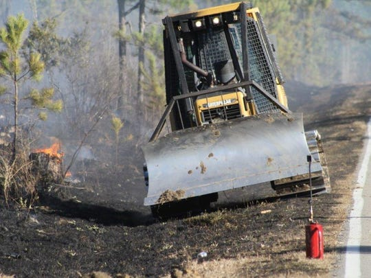 A state Forestry Commission fire crew works to stop