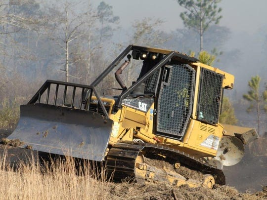 State Forestry Commission firefighters make a cut to stop a forest fire threatening homes in Harrison County. The agency is laying off 25 workers and eliminating six positions.