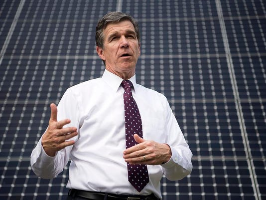 636082675264660825-Roy-cooper-with-solar-panels.jpg