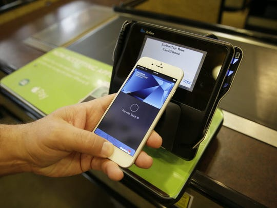 n this photo taken Friday, Oct. 17, 2014, Eddy Cue, Apple Senior Vice President of Internet Software and Services, demonstrates the new Apple Pay mobile payment system at a Whole Foods store in Cupertino, Calif.