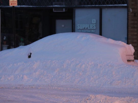 Snow-buried car on Fairfax Road in Rochester.