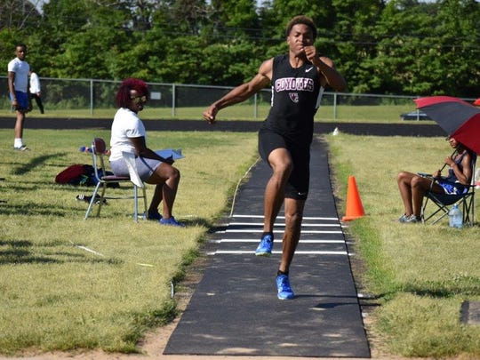 A West Creek athletes competes in the triple jump during