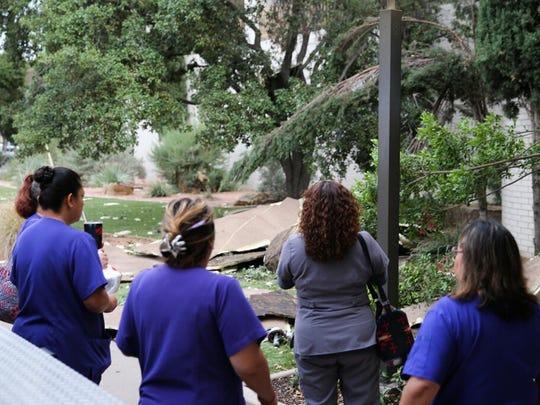 People gather around to view roof debris scattered  in front of Shannon Medical Center's main building ripped off during a storm hit San Angelo Friday, June 23, 2017.