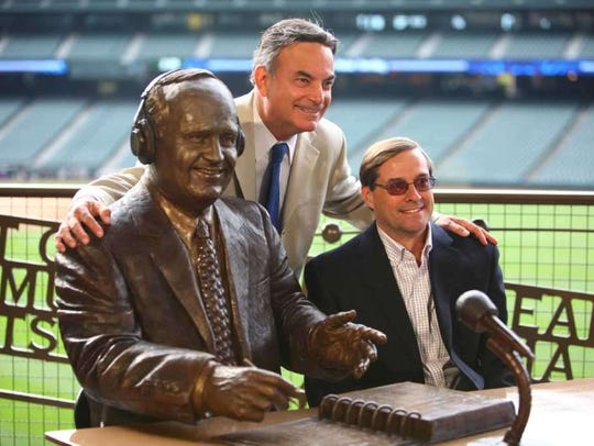 Kevin Cremin, right, and Rick Rizzs with the statue