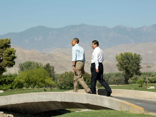 President Barack Obama and Chinese President Xi Jinping stroll over a pedestrian bridge near a pond, with the San Jacinto Mountains in the distance, during their meeting at the Sunnylands estate in Rancho Mirage in June 2012.