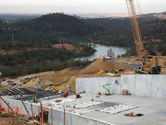 Crews work to repair the damaged main spillway of the