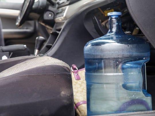 Phoenix resident Diana Garcia fills water jugs to take