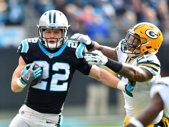 Panthers running back Christian McCaffrey (22) runs past Packers strong safety Josh Jones (27) during their 2017 game in Charlotte, N.C.