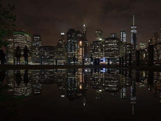 The Manhattan skyline is reflected in the East River