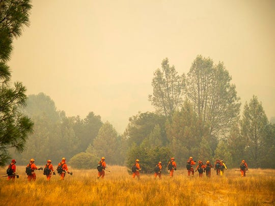 An inmate crew battles a wildfire in Spring Valley, Calif., Sunday, June 24, 2018. Wind-driven wildfires destroyed buildings and threatened hundreds of others Sunday as they raced across dry brush in rural Northern California.