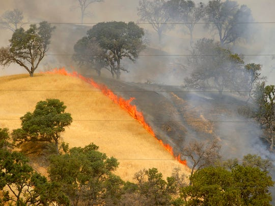 Fire burns the hillsides as the County Fire continues