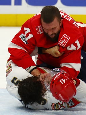 Red Wings forward Luke Glendening fights the Panthers' Aaron Ekblad during the second period of the Wings' 2-1 overtime loss on Monday, Dec. 11, 2017, at Little Caesars Arena.
