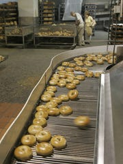 Bagels slide onto a conveyor belt in the production