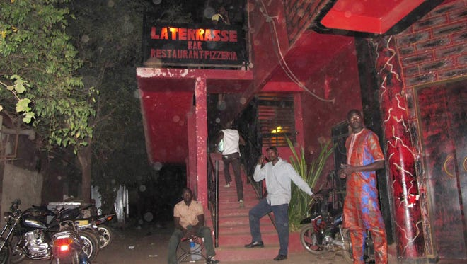 Unidentified locals stand outside 'La Terrasse' bar where a gunman opened fire in  Bamako, Mali.
