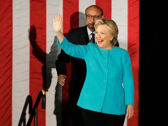 Khizr Khan, top left, a Gold Star father, whose son Army Captain Humayun Khan was killed in Iraq saving his fellow soldiers, and Democratic presidential candidate Hillary Clinton, right, wave as they take the stage during a campaign rally, Sunday, Nov. 6, 2016, in Manchester, N.H.