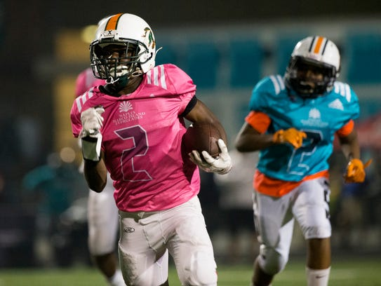 Team Tampa's Joquez Smith (2) carries the ball against