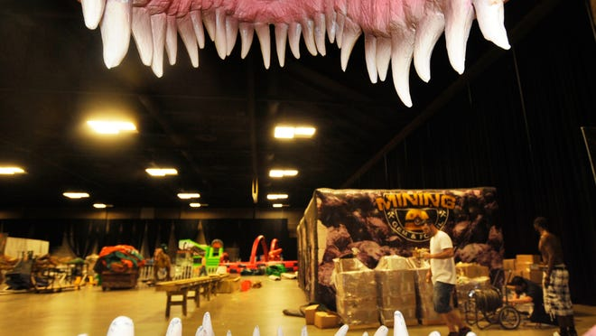 Crew set up Discover the Dinosaurs on Thursday at the Visalia Convention Center.