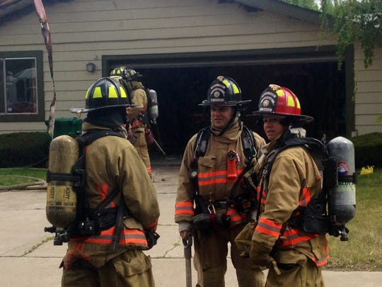 Firefighters assess the scene outside a  Reno house.