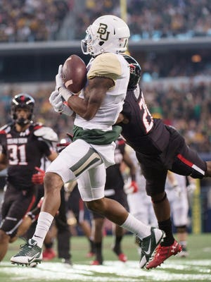 Baylor Bears running back Corey Coleman (1) catches a pass for a touchdown as Texas Tech Red Raiders defensive back Tevin Madison (20) defends during the first half at AT&T Stadium.