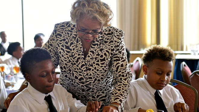 Gwendolyn Chess helps Jaquarius Scott, 11, left, and Quenterius Gardner, 12, with the finer points of silverware handling Wednesday during an etiquette class at the Capital Club in Jackson.