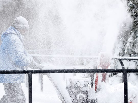 A workers clears snow from the Titletown District ice