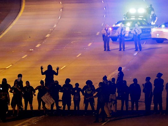 In this Thursday, Sept. 22, 2016 file photo, protesters block I-277 during a third night of unrest following Tuesday's police fatal shooting of Keith Lamont Scott in Charlotte, N.C. Protesters who have filled the streets to push for the release of video of Scott's shooting could see their task get much harder if Charlotte authorities do not share the footage within a week. A North Carolina law that takes effect Oct. 1 will declare that the video is not a public record and that only a judge can release it.