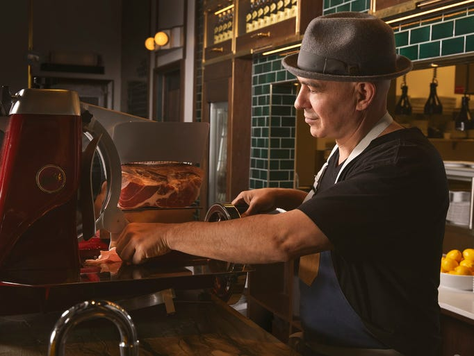 Michael Symon slices meat at Angeline at the Borgata.