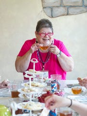 Kim Seeber laughs while sipping tea during a tea party at Mulberry Jean's Accents on Saturday.