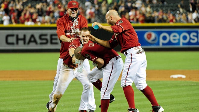 Arizona Diamondbacks left fielder Cody Ross (7), shortstop Chris Owings (16) and starting pitcher Daniel Hudson (41) dump water and sports drink bottles on center fielder Tony Campana (19) in celebration after Campana hit a RBI single in the 9th inning to defeat the Milwaukee Brewers at Chase Field on June 18, 2014.