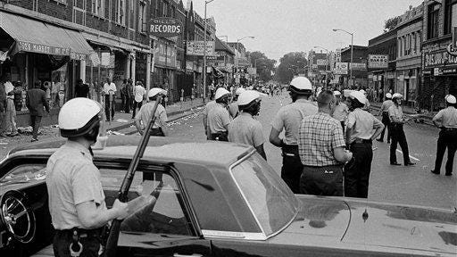 "Police blockade a street on Detroit's Near West Side, about three miles from the downtown area, throwing stones and bottles at store fronts, and looting July 23, 1967. Violence erupted early when police raided an unlicensed after-hours bar known as a ""blind pig."""