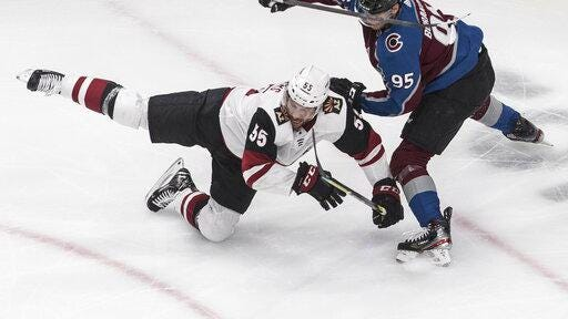 Arizona Coyotes' Jason Demers , left, is taken down by Colorado Avalanche's Andre Burakovsky during the third period of a Stanley Cup first-round playoff series on Wednesday in Edmonton, Alberta.