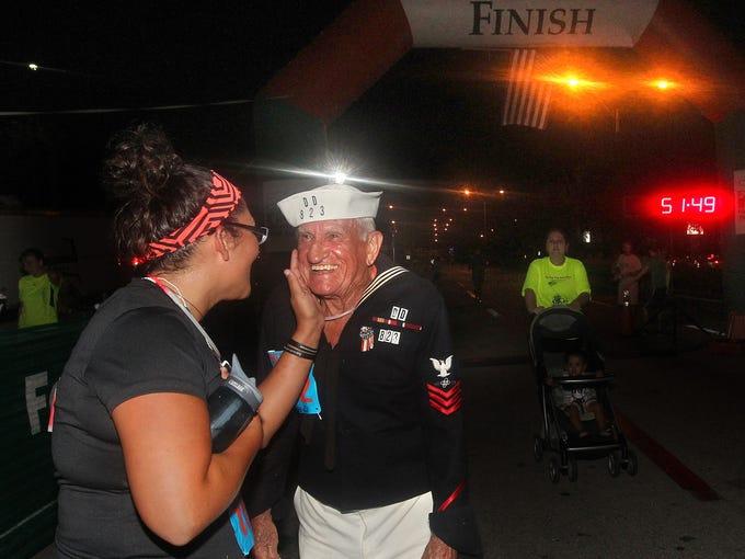 Army veteran Laura Hartman, left, congratulates Navy