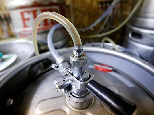 Beer flows from a keg at Farmhouse Brewery in Owego. The tasting room offers more than 15 beers on tap.