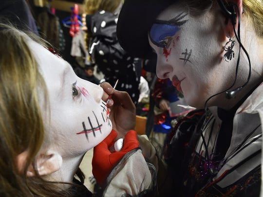 Portraying the Queen of Hearts character, Stacie Tucker applies costume make-up to her daughter Mackenzie, the Grim Reaper, in preparation for the Haunted Mansion on Saturday, Oct. 14, 2017. Both are volunteers.