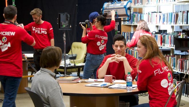 Lansing High alum Clara Montague (lower right) talks with the actors appearing in her film for the national Coca-Cola and Regal Films Competition entry while the crew sets up for the next shot. Clara and her partner Eva Kirie are first year students at Ithaca College and one of five teams picked as finalists for the national contest.