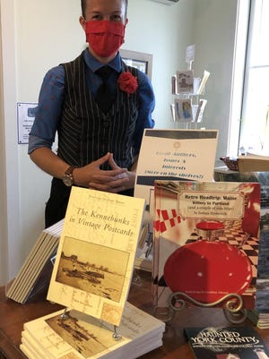 """Cynthia Walker, the executive director of the Brick Store Museum, is seen here on Tuesday alongside a display of the museum's new book, """"The Kennebunks in Vintage Postcards."""""""