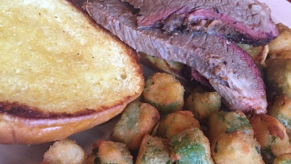 Graham Lyle Jr. said the beef brisket, served here on a sandwich with a side of fried okra, is the signature dish at Graham's Smokehouse in Cape Canaveral.