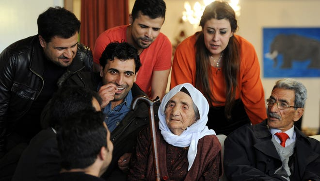 107-year-old Syrian Sabria Khalaf, center, sits on a sofa with members of her family in Holdorf, northern Germany, Monday, March 17, 2014.