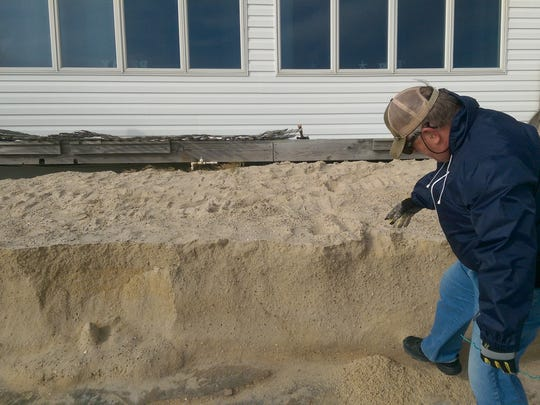 Bowers Beach councilman Bob McDevitt examines erosion just outside his bayfront home Monday after days of high tides and northeast winds.