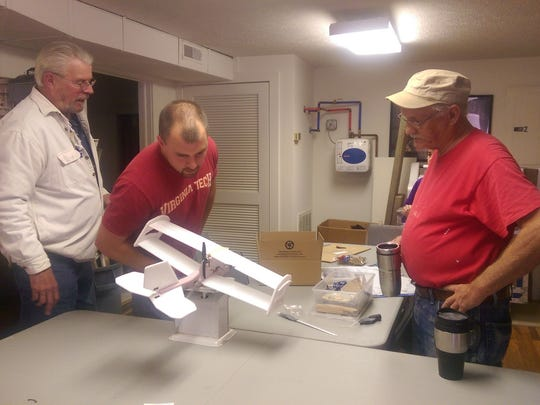 Nelson Patterson, Tyler Patterson and Rick Hubbard weigh remote controlled airplanes built at the Staunton Makerspace.